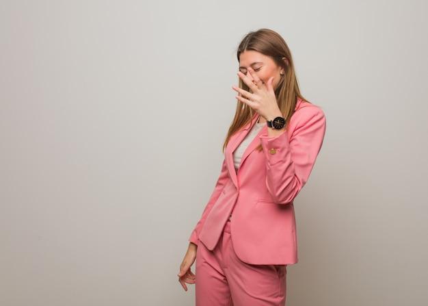 Joven rusa de negocios avergonzada y riendo al mismo tiempo
