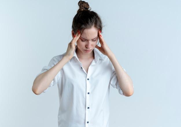 Joven rusa rubia cansada sostiene la cabeza aislada en el espacio en blanco con espacio de copia