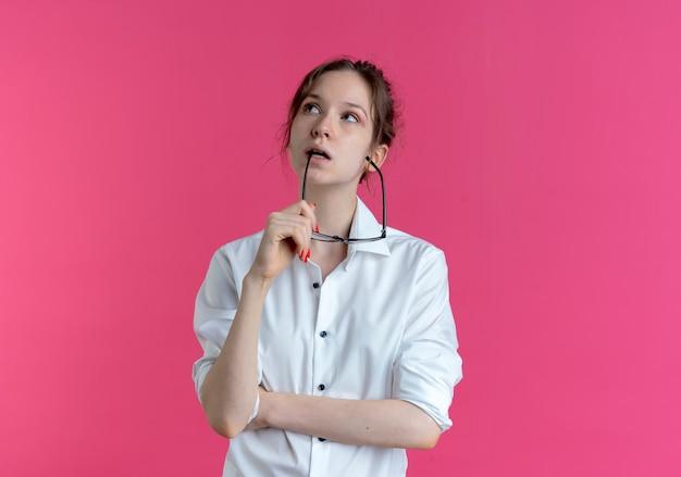 Joven rusa rubia pensativa sostiene anteojos ópticos cerca de la boca mirando hacia arriba aislado en el espacio rosa con espacio de copia