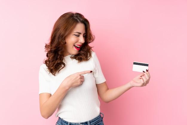 Joven rusa sobre aislado sosteniendo una tarjeta de crédito