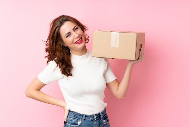 Joven rusa sobre fondo rosa aislado sosteniendo una caja para moverlo a otro sitio