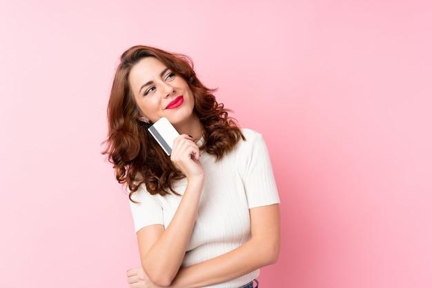 Joven rusa sobre rosa aislado sosteniendo una tarjeta de crédito