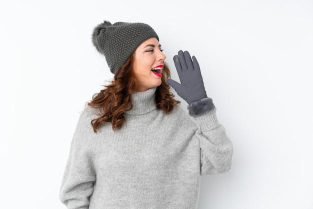 Joven rusa con sombrero de invierno sobre gritos blancos aislados con la boca abierta