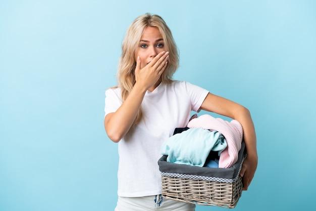 Joven rusa sosteniendo una canasta de ropa aislada en azul cubriendo la boca con las manos