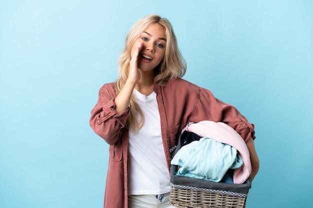 Joven rusa sosteniendo una canasta de ropa aislada en azul gritando con la boca abierta