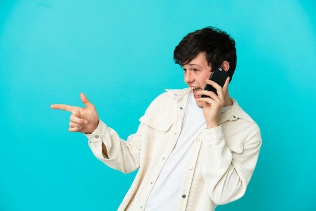 Joven ruso con teléfono móvil aislado sobre fondo azul apuntando con el dedo hacia un lado y presentando un producto
