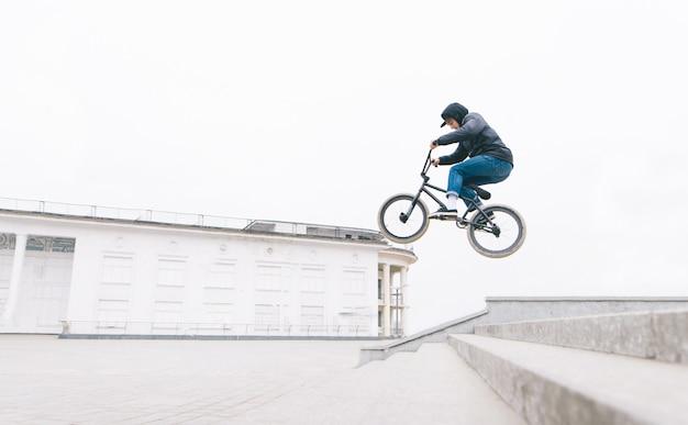 Joven salta en el bmx desde las escaleras contra el telón de fondo de un paisaje urbano minimalista