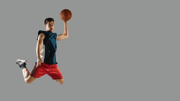 Joven saltando mientras jugaba baloncesto con espacio de copia