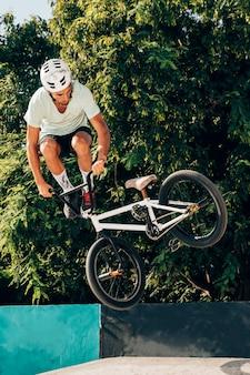 Joven saltando con tiro largo de bicicleta bmx