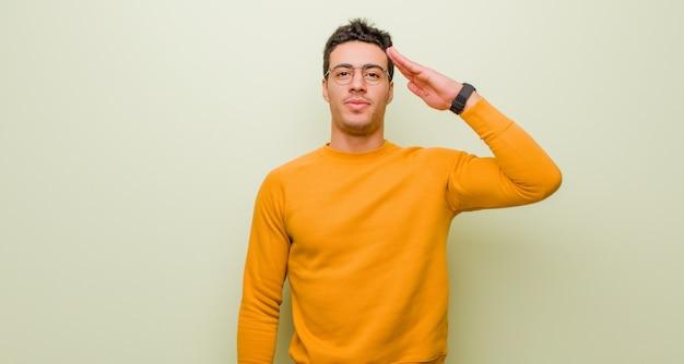 Joven saludando a la cámara con un saludo militar en un acto de honor y patriotismo, mostrando respeto contra la pared