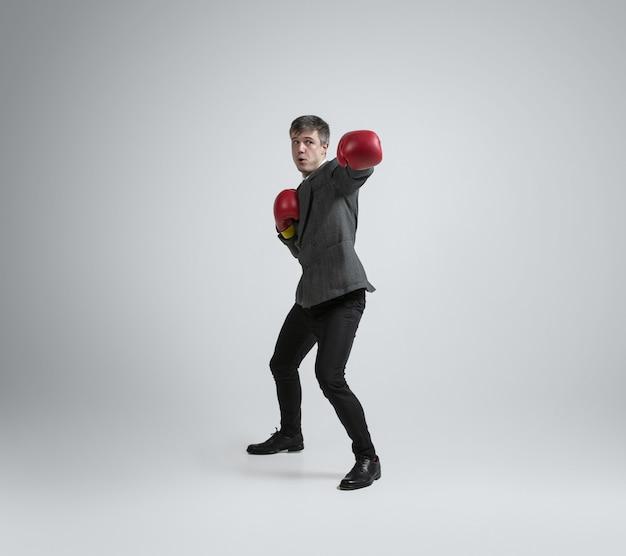 Joven y salvaje. hombre caucásico en ropa de oficina de boxeo con dos guantes rojos en la pared gris. formación de empresario en movimiento, acción. aspecto inusual para deportista, actividad. deporte, estilo de vida saludable.