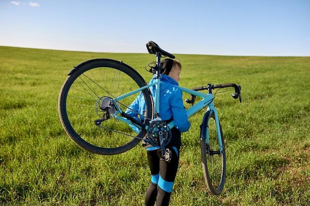 Un joven sano que lleva su bicicleta de carretera sobre su hombro