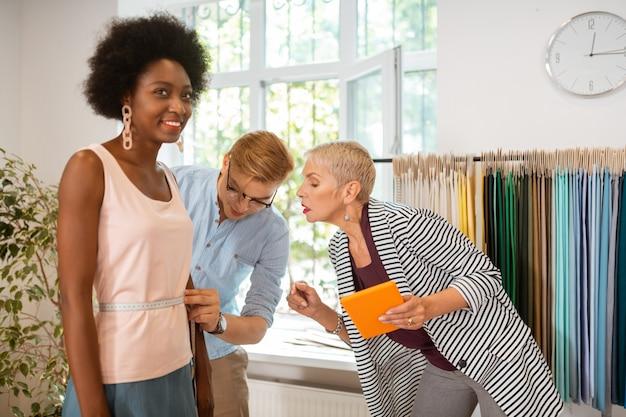 Joven sastre concentrado midiendo atentamente la cintura de los jóvenes modelos