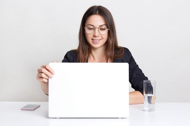 Una joven satisfecha se sienta frente a una computadora portátil abierta, mira un seminario web, piensa en crear un nuevo diseño web, usa gafas redondas para una buena visión, bebe agua, se sienta sola en interiores.