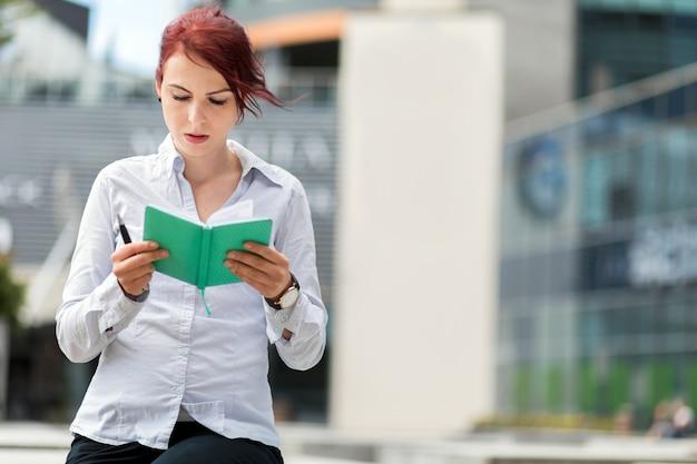 Joven secretaria leyendo su agenda al aire libre