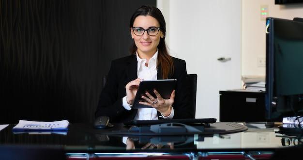 Joven secretaria pensativa usando una tableta digital en su escritorio