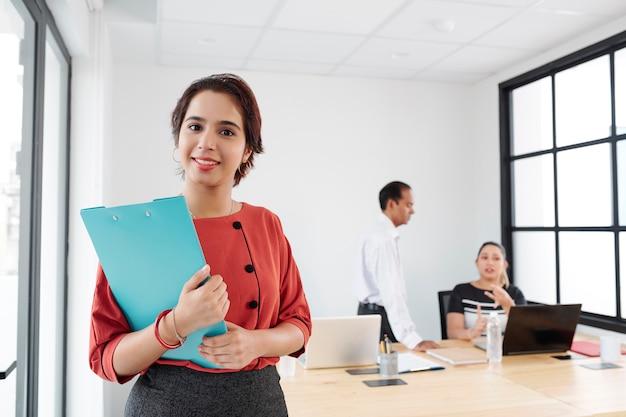 Joven secretaria de pie en la oficina
