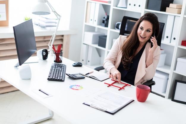 Una joven sentada en la computadora vieja, hablando por teléfono y sosteniendo un lápiz rojo.