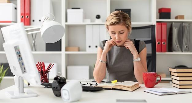 Una joven está sentada en una mesa en la oficina. antes de que la niña mienta un libro abierto.