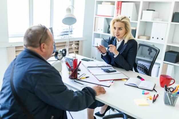 Una joven está sentada en una mesa de la oficina, sosteniendo unas gafas en la mano y hablando con un hombre.
