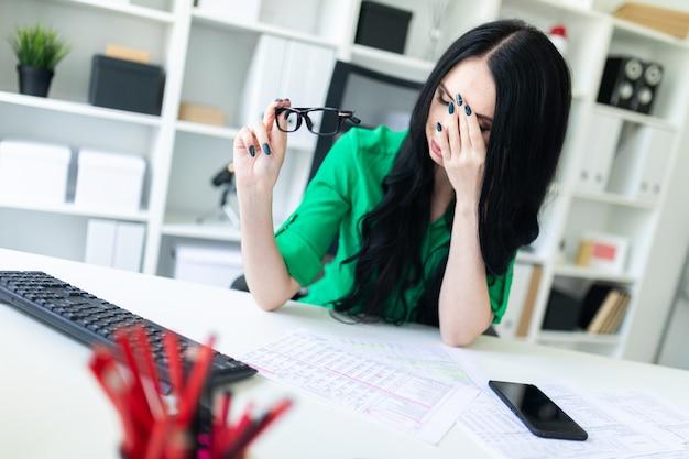 Una joven está sentada en la oficina de la mesa, frotándose la cara y sosteniendo los lentes en la mano.