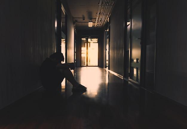 Joven sentado abraza su rodilla solo en la oscuridad en la pasarela de la oficina. hombre triste y serio