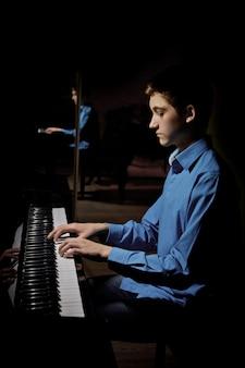 Joven sentado al piano.