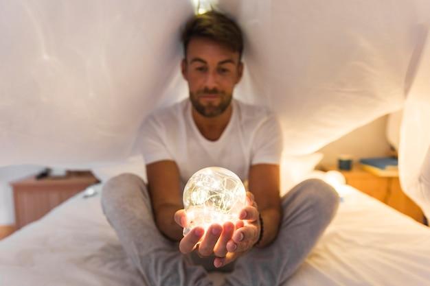 Joven sentado bajo la cortina en la cama sosteniendo la esfera iluminada en la mano