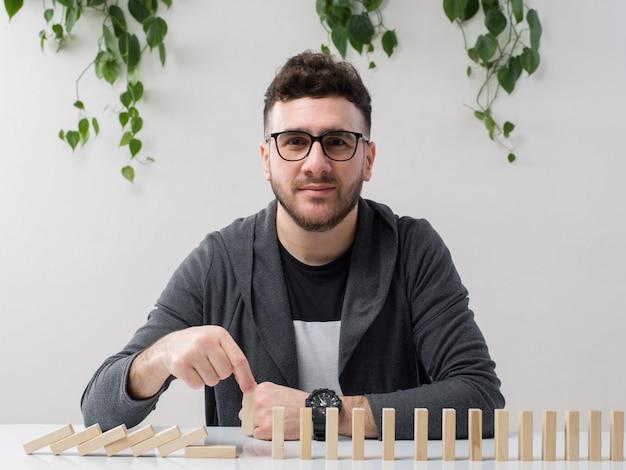 Joven sentado en gafas relojes chaqueta gris jugando con pequeñas figuras de madera junto con planta en blanco