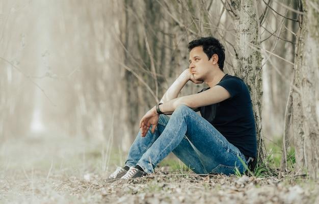 Joven sentado junto a un árbol en el bosque pensando en la vida y descansando.