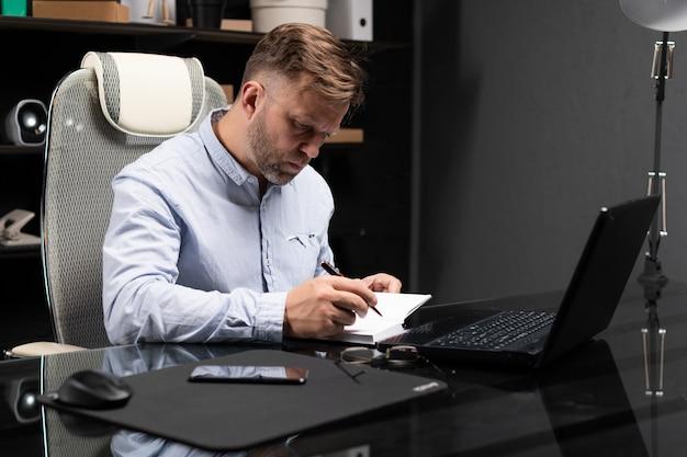 Joven sentado en la mesa de la computadora y toma notas en el diario
