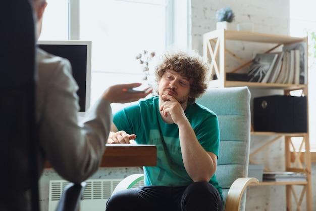 Joven sentado en la oficina durante la entrevista de trabajo con empleada, jefe o gerente de recursos humanos, hablando, pensando, se ve confiado
