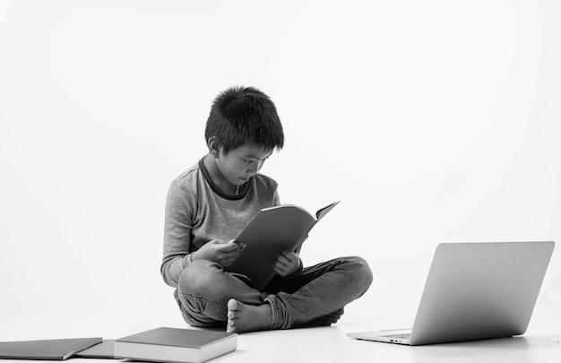 El joven sentado en la planta baja, leyendo un libro con sentimiento de interés, tono blanco y negro