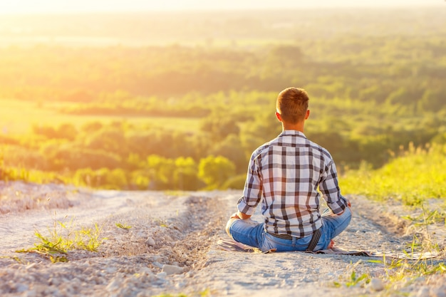 Joven sentado en posición de loto con hermosa vista al atardecer