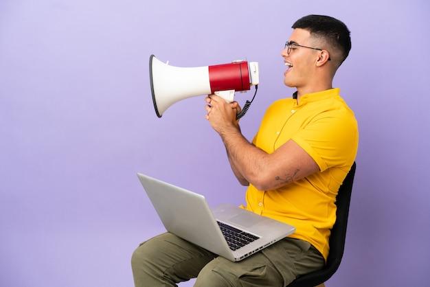 Joven sentado en una silla con un portátil gritando a través de un megáfono