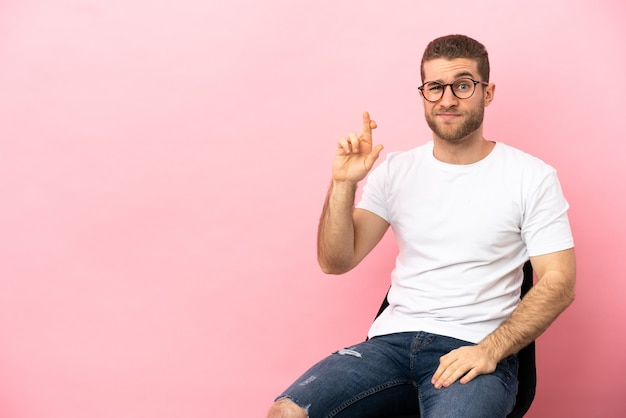 Joven sentado en una silla sobre fondo rosa aislado con los dedos cruzando y deseando lo mejor
