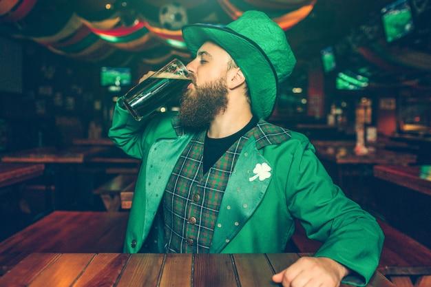 Un joven sentado solo a la mesa en el pub. bebe cerveza oscura de la taza. el tipo usa el traje de san patricio.