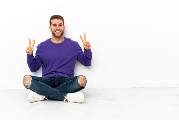 Joven sentado en el suelo mostrando el signo de la victoria con ambas manos
