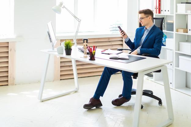 Un joven está sentado con un teléfono en sus manos en una mesa en la oficina.