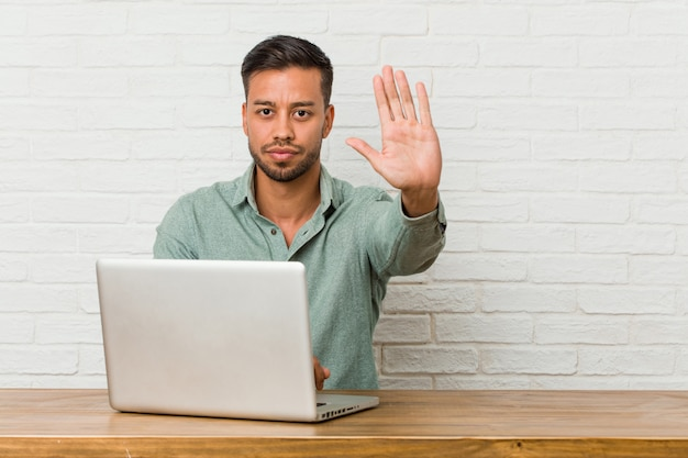 Joven sentado trabajando con su computadora portátil de pie con la mano extendida que muestra la señal de stop, evitando que