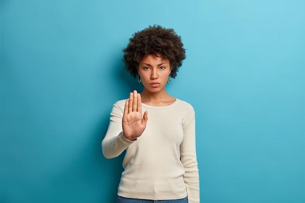 Joven seria de piel oscura muestra el símbolo de prohibición de la señal de pare mantiene la palma hacia adelante