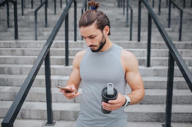 Joven serio y musculoso está parado en las escaleras y mira el teléfono que tiene en una mano