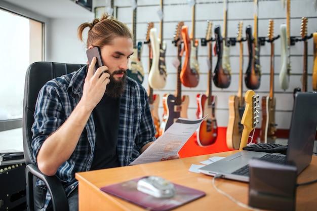 Joven serio trabaja a la mesa en la sala. mira el documento que tiene en la mano y habla por teléfono. muchas guitarras eléctricas colgando detrás de él.
