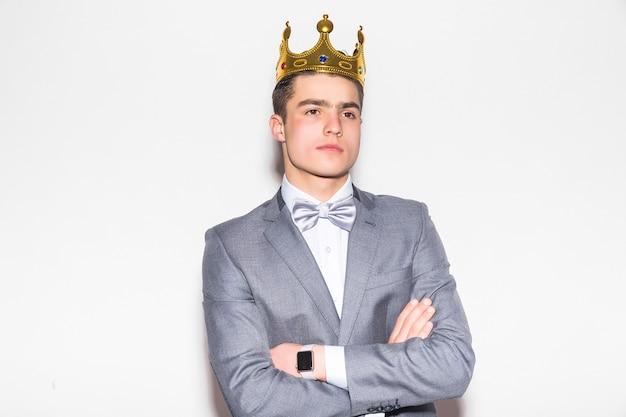 Joven serio con traje y corbata, sosteniendo una corona de oro sobre su cabeza, en la pared blanca