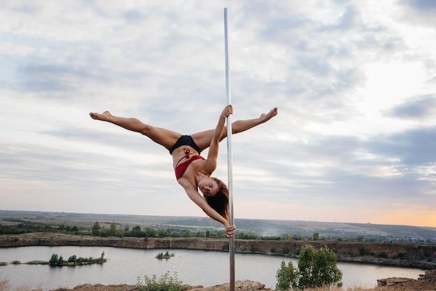 Una joven sexy realiza ejercicios increíbles en un poste durante una hermosa puesta de sol. baile. sexualidad.