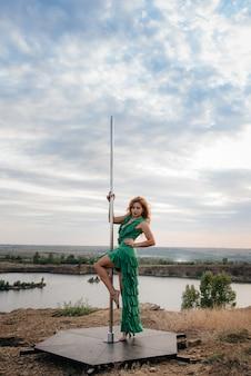 Una joven sexy realiza ejercicios increíbles en poste durante una puesta de sol. baile. sexualidad.
