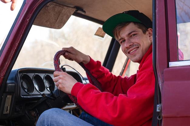 Joven se sienta en el asiento del conductor de un automóvil rojo, con la mano en el volante. conceptos vacaciones y viajes, vehiculo.