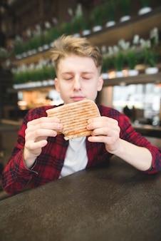 Un joven se sienta en un café y sostiene un sándwich de panini. un estudiante sirve un sándwich en un café.