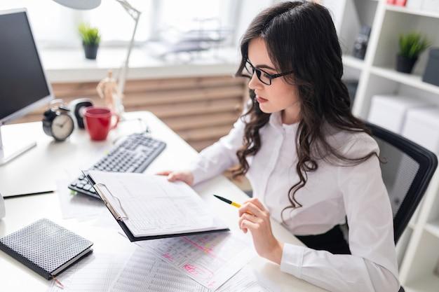 Una joven se sienta en el escritorio de la oficina y revisa los documentos.
