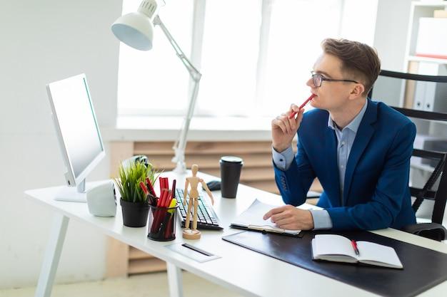 Un joven se sienta en una mesa de la oficina, sostiene un bolígrafo rojo en la mano y trabaja con documentos.